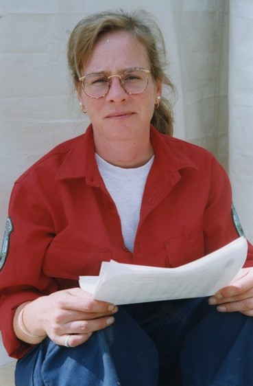 Seated blonde woman with glasses looks at the camera. She is holding a paper.