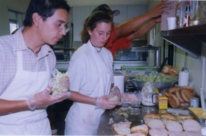 Man and woman in white aprons make sandwiches in a kitchen.