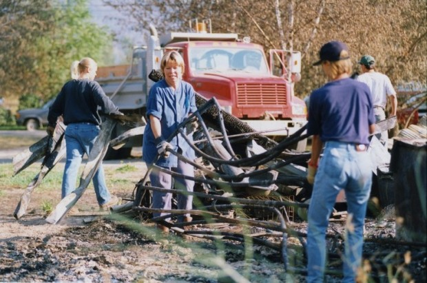 Two women lift twisted metal from a pile. Another teenager carries metal towards a red dump truck.
