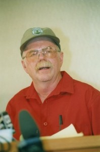 Man wearing a baseball hat speaks to microphones.
