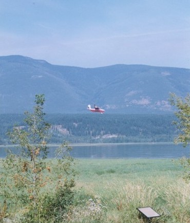 Aeroplane flying over the lake. Hills in the background.