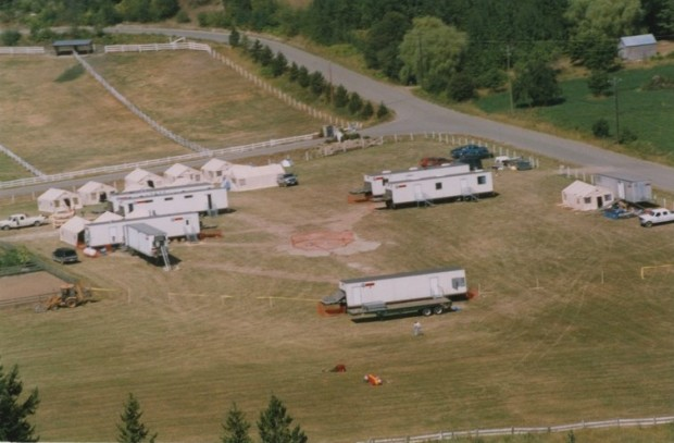 Aerial view of trailers, tents, and a landing pad in a field.