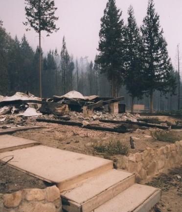 Une fondation en pierres, blocs de ciment et du métal tordu après le feu.