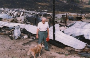Man and dog stand in front of rubble and twisted metal.