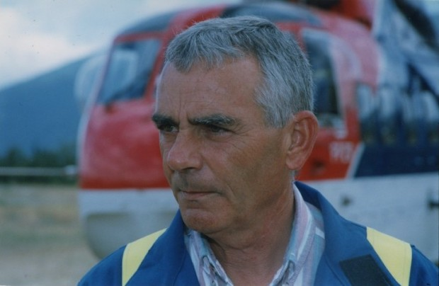 Portrait of a serious looking man wearing coveralls. Helicopter in background.