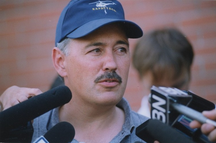 Portrait of a mustached man in a blue baseball cap speaking into microphones.