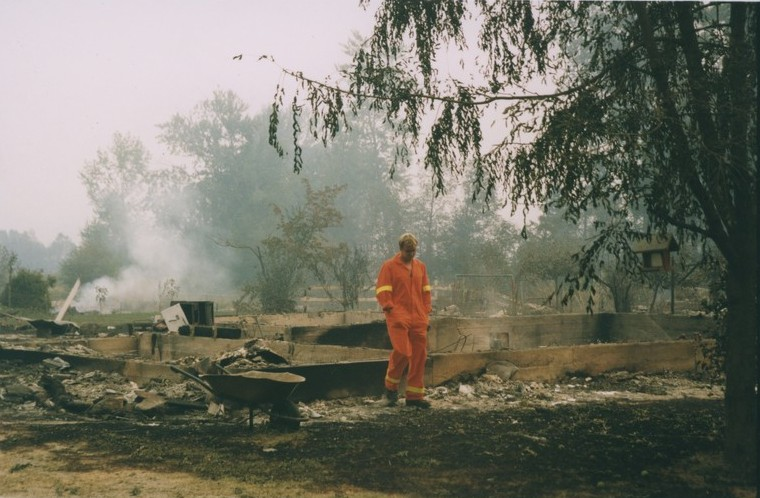 Fireman walks through burning embers. A building's foundation is all that is left after the fire.