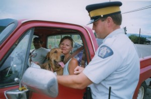 Woman with her dog in her lap sits in a red pick-up truck. RCMP officer talking to her. Another passenger in the truck sits with a dog in his lap.