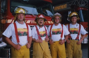 Four firefighters stand in front of their fire trucks.