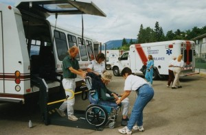Two workers and a uniformed person assist a man in a wheelchair. Others are walking to and from the front of the bus. Two ambulances in background.