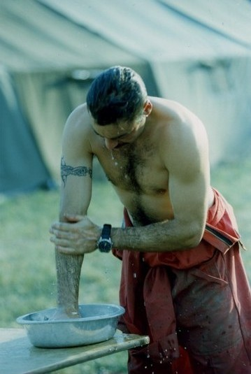 Man stripped to the waist washing his arm in a basin on a table. Hair is wet. Coveralls are dirty. Tents in background