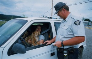RCMP officer with printed information talking to a woman in a white vehicle at the side of a road. Driver has a dog in her lap.