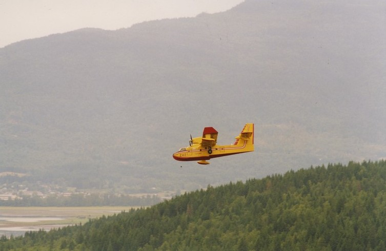 Yellow aircraft in flight above green forest. Hill in background.