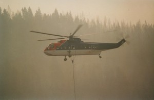Helicopter in flight in a smoke filled sky. Cable hangs from the aircraft. Forest in background.