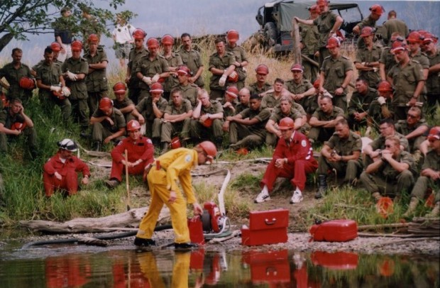Group of soldiers and forestry personnel watch a man in yellow coveralls operate a water pump. Most wear hard hats. Water in foreground.
