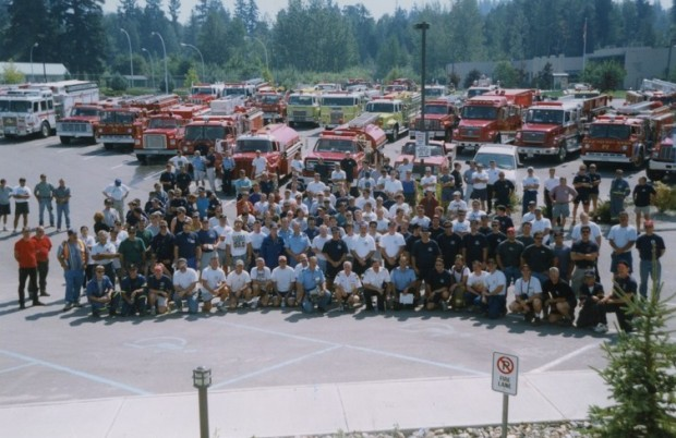 Firefighters assemble in front of fire engines and tenders for a group photo.