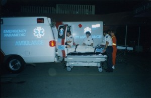 Three ambulance attendants loading a person on a stretcher into an ambulance. Emergency worker in orange outfit with reflective stripes looks on.