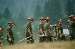 Soldiers walking through a field wearing orange hard hats and carrying shovels and grub hoes. One soldier looks at the camera.