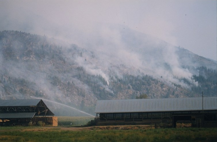 Fire burning in the hills behind a farm. Hay barns in foreground. Water being sprayed on fields.