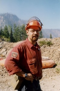 Man with a goatee and glasses wearing a hard hat. Forest and hills behind him.