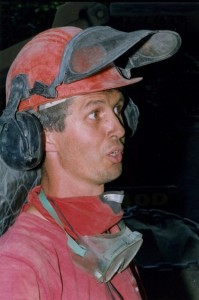 Man in a red shirt with a mask and goggles around his neck, wearing a hard hat talking.