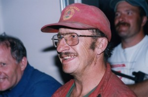 Mustached man in coveralls, wearing a red Fire Warden baseball cap smiles.