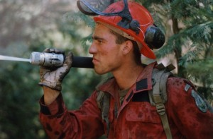 Man in coveralls and a helmet holds a hose over his shoulder and sprays something out of sight.