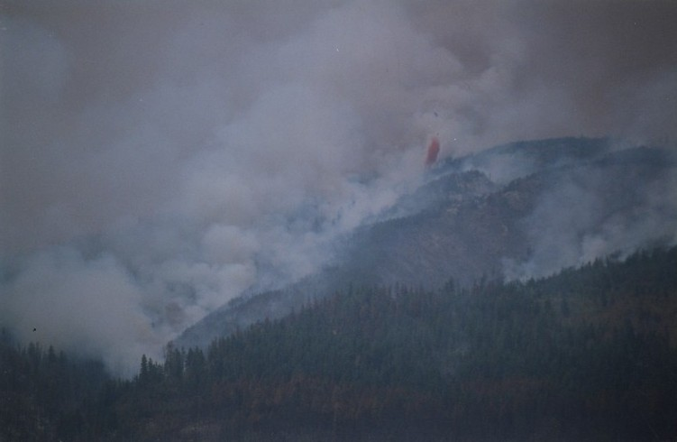 Fire in hills. Red fire retardant being dropped from a helicopter.