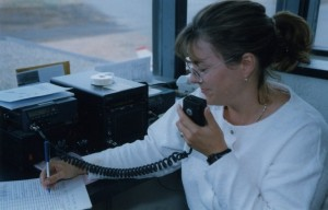 Seated at a desk, woman with a pony tail and glasses speaking into a speaker of a radio and entering information on a sheet.