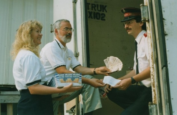 Man and woman present several hundred dollar bills, a cheque and juice boxes to Salvation Army officer.