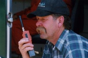 Man in a blue and white checked shirt and blue baseball cap speaking into a hand held radio.