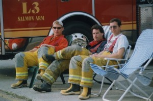 "Three men in firefighter's pants and rubber boots sit in lawn chairs beside a fire engine labeled ""L3""."