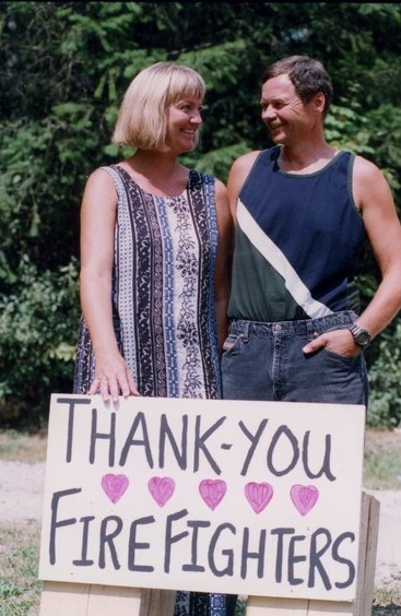"Woman and man smile at each other. She is balancing a sign that says, ""Thank you firefighters."""
