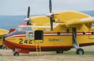 Yellow plane with red and white stripe, dual propellers, Numbered 242 and Quebec on its belly.