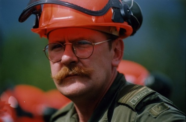 Mustached man in green uniform, wearing a hard hat and glasses squints at the camera.