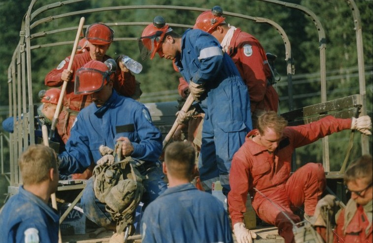 Men in coveralls, some with hard hats, carrying shovels and backpacks, getting out of an uncovered army truck.