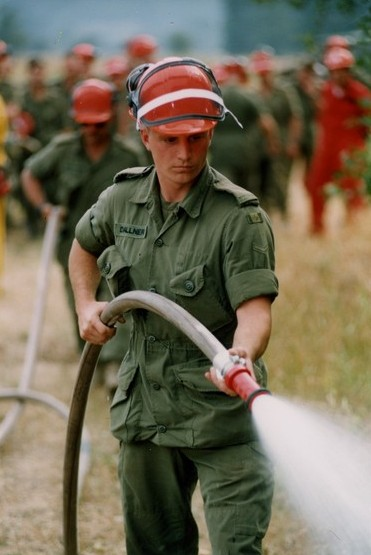 Soldier in uniform wearing a hard hat holds hose spraying water.