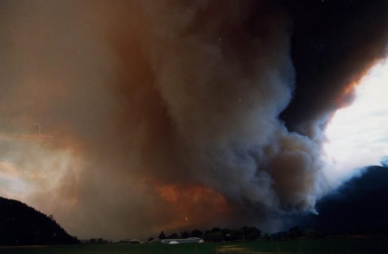 Fumée s'élève des collines. Ciel de couleur orangée. Ferme au centre de la photo.