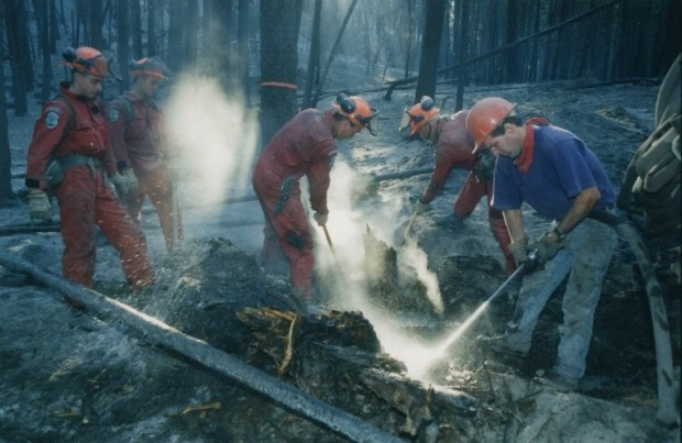 Two firefighters in red coveralls dig in the burned ground. A man with a purple t-shirt sprays water into the ground. Two men in red coveralls look on. All men wear hard hats.