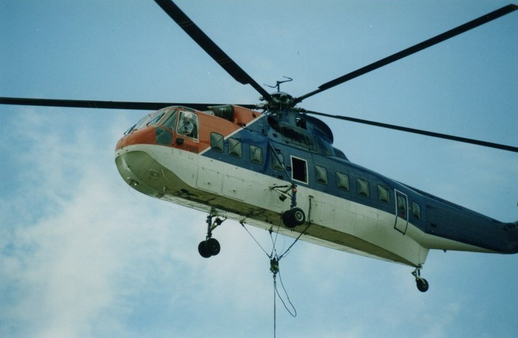 A helicopter in flight. Cable suspended from it.