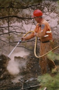 Man in yellow coveralls and hard hat sprays hose into fire.