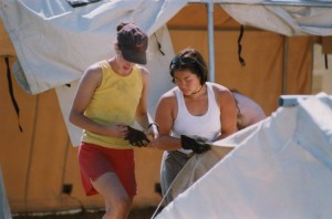 Two women dressed in summer clothing setting up tents.