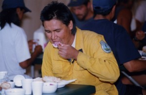 Man in yellow overalls sits at a table eating a meal.