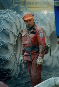 Man wearing red coveralls and hard hat stands in front of two tires belonging to a piece of large equipment. Tires have chains.