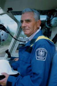 Man in blue coveralls seated with hard hat in hand, seated in a helicopter cabin.