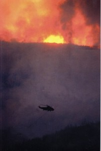 A helicopter hauling a water bucket approaches a blazing fire.