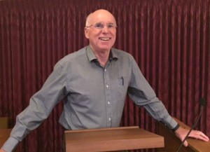 Man in a grey shirts smiles, standing at a lectern.