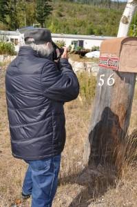 Photographe prenant une photo d'un boîte à lettres rurale.