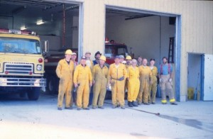 14 firefighters assemble in front of the firehall.