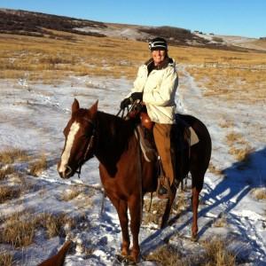 Femme assise sur un cheval sellé en hiver.